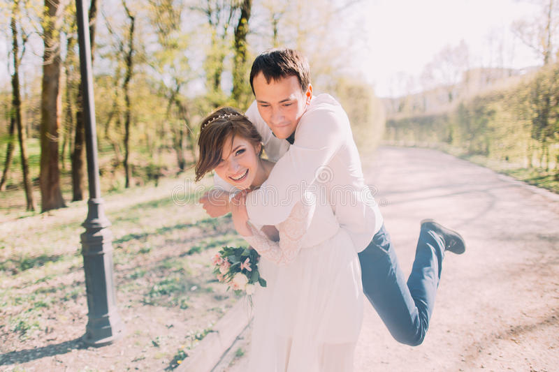 Smiling bride carrying on back groom outdoors in spring park royalty free stock photography