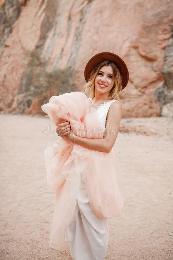 Smiling bride in hat stands and holds hem of her long dress in canyon. Smiling bride in hat stands and holds hem of her long dress in canyon on background of royalty free stock images