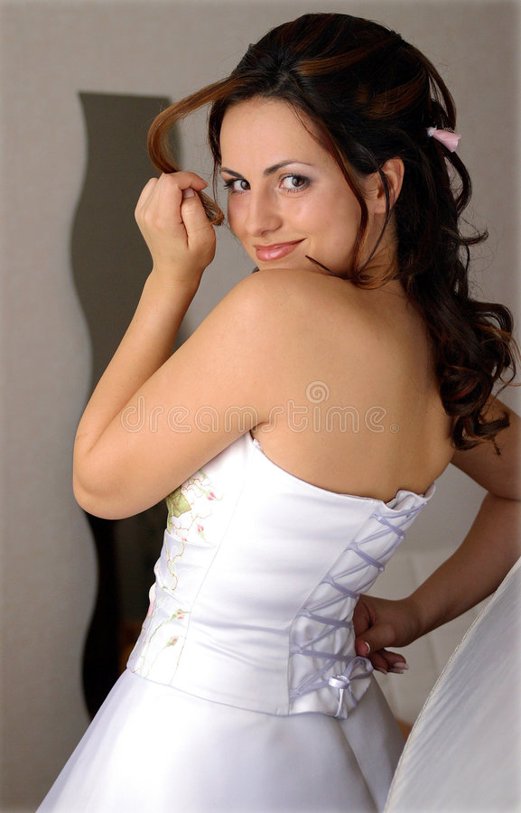 Smiling bride in white dress. Half body portrait of smiling bride in white dress, isolated on light background stock image