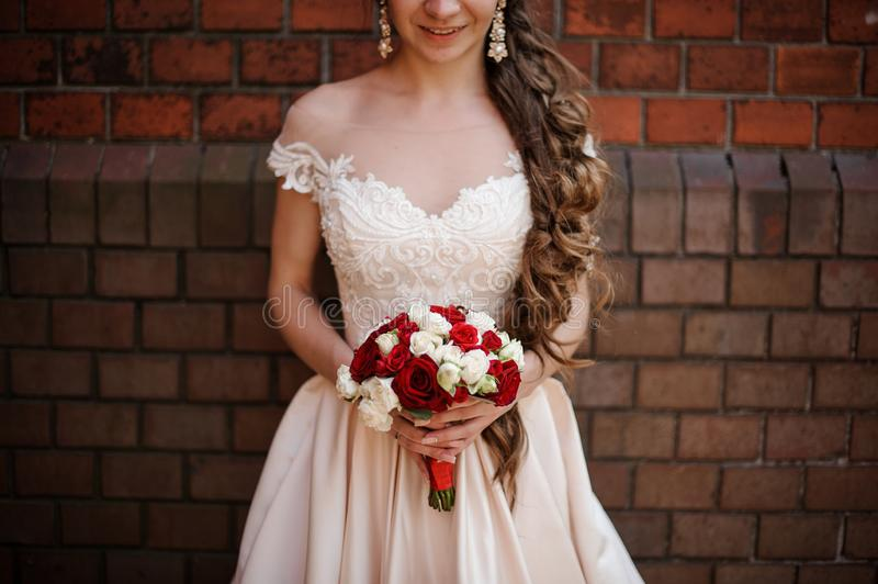 Smiling bride in white wedding dress with a bouquet of red and white roses stock image