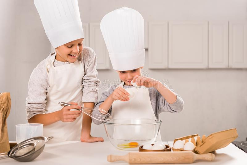 Smiling brother and sister in aprons and chef hats during food preparation at table. In kitchen stock photography