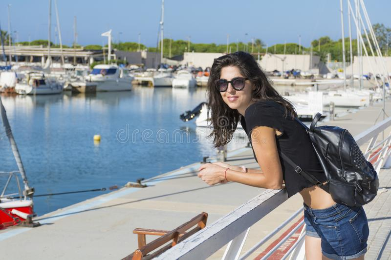 Young Beautiful Woman on a Port in Spain. Smiling brunette beautiful woman on a boats background stock images