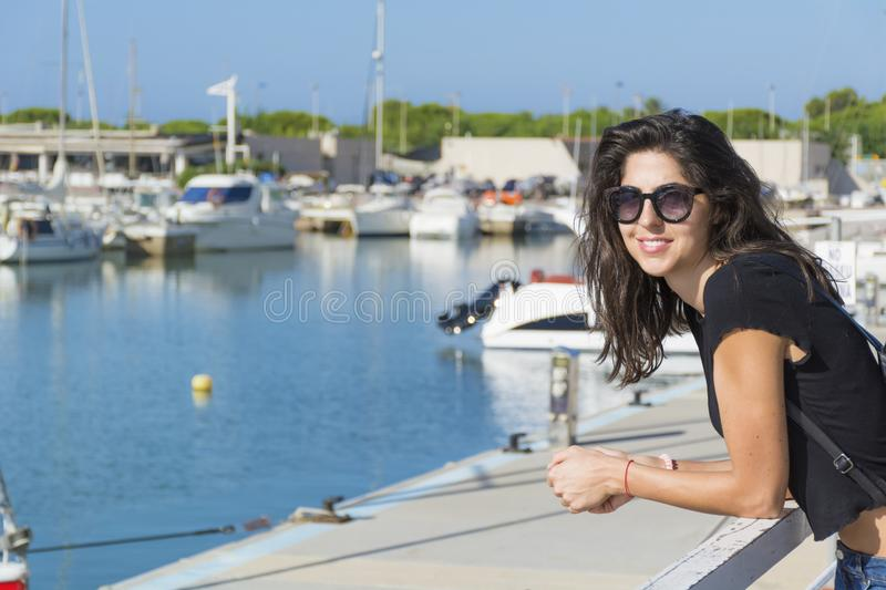 Young Beautiful Woman on a Port in Spain. Smiling brunette beautiful woman on a boats background stock image