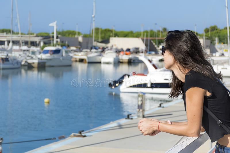 Young Beautiful Woman on a Port in Spain. Smiling brunette beautiful woman on a boats background royalty free stock photography