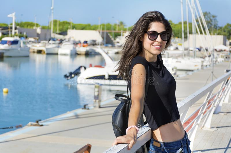 Young Beautiful Woman on a Port in Spain. Smiling brunette beautiful woman on a boats background royalty free stock image