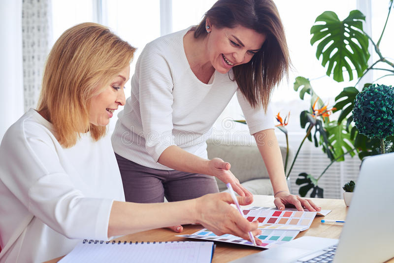 Download Smiling Brunette And Blonde Working With Catalog Of Color Palett Stock Image - Image of color, communication: 92490799