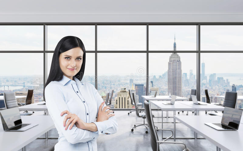 Smiling brunette business lady with cross hands is standing in a modern panoramic office in New York City. Manhattan panoramic vie. W. Workplaces are on the royalty free stock images