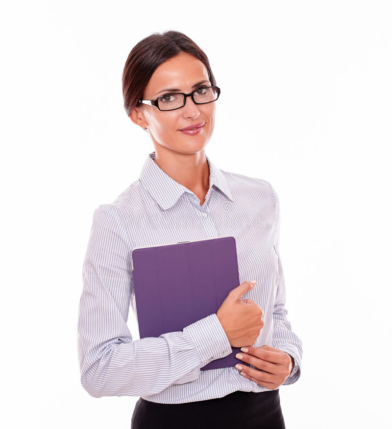 Smiling brunette businesswoman carrying a tablet stock photography