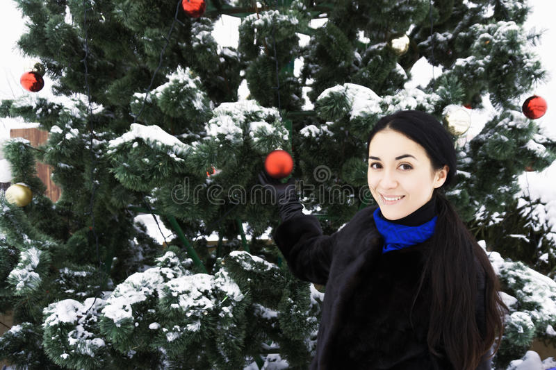Smiling brunette at the christmas tree stock photo