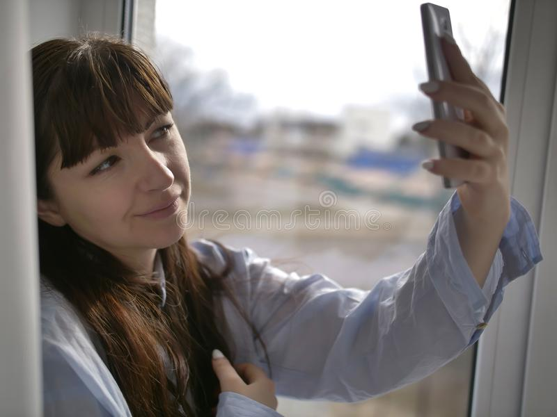 Smiling brunette girl in a blue shirt makes selfie by the window. Smiling girl in a blue shirt makes selfie by the window royalty free stock photo