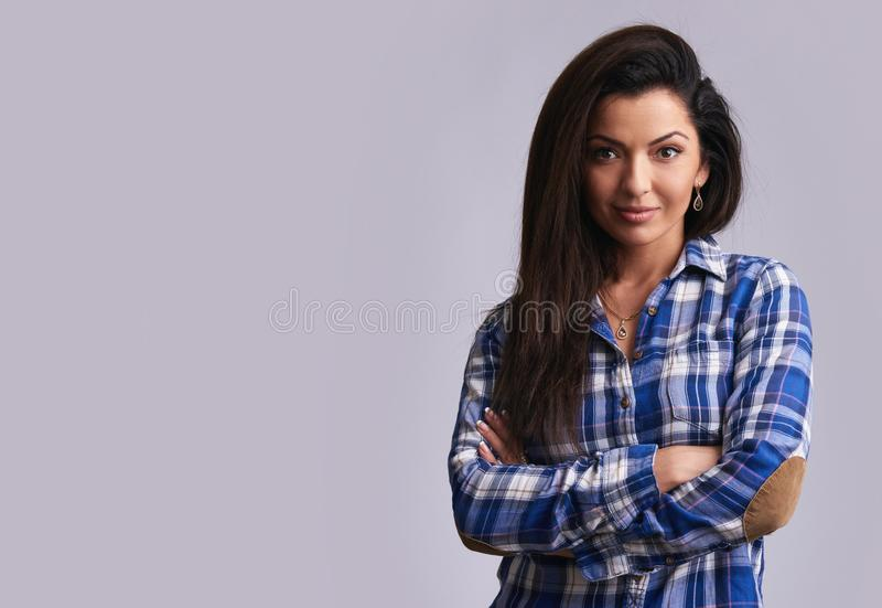 Smiling brunette girl wearing casual shirt. Isolated. Smiling brunette girl wearing casual shirt. Confident woman with arms crossed. Isolated on grey royalty free stock photo