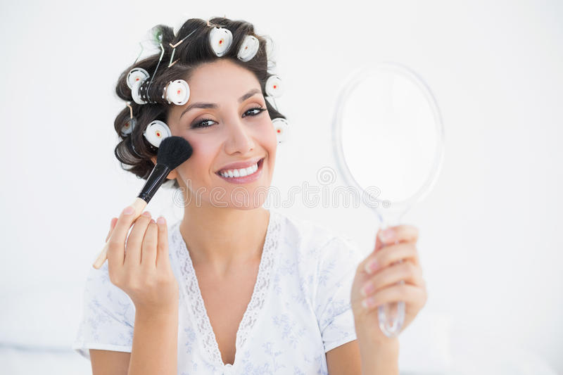Download Smiling Brunette In Hair Rollers Holding Hand Mirror And Applyin Stock Photo - Image: 33050336