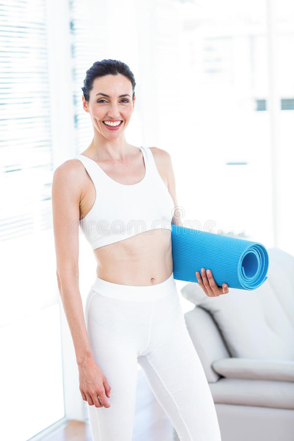 Smiling brunette holding exercise mat. In the living room stock photos