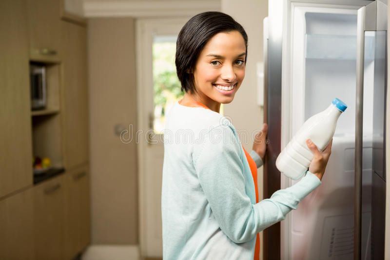 Smiling brunette holding milk bottle with open refrigerator. In the kitchen stock image