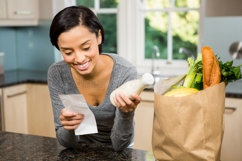 Smiling brunette holding receipt and milk. In the kitchen stock photos