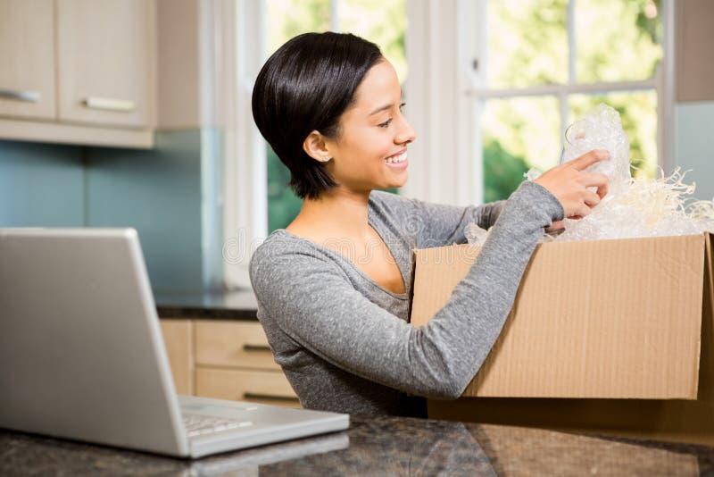 Smiling brunette opening box royalty free stock image