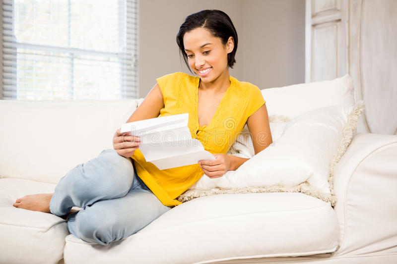 Smiling brunette reading document. On the sofa royalty free stock image