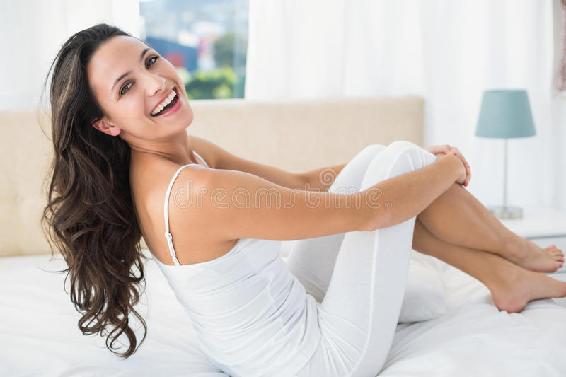 Smiling brunette sitting on bed. At home in bedroom stock photos