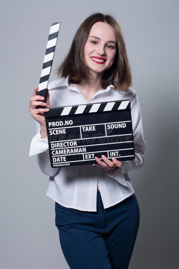 Smiling brunette in white blouse with movie crackers. Assistant director with a clapperboard on a gray background stock photos