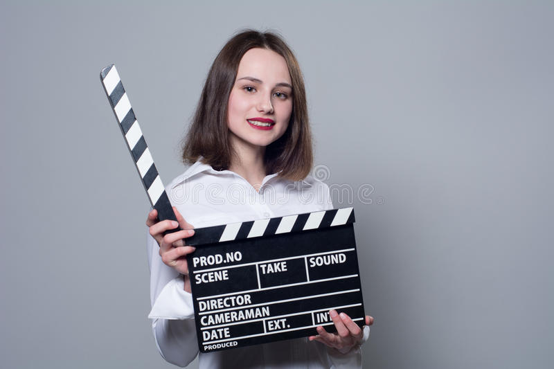 Smiling brunette in white blouse with movie crackers. Assistant director with a clapperboard on a gray background royalty free stock image