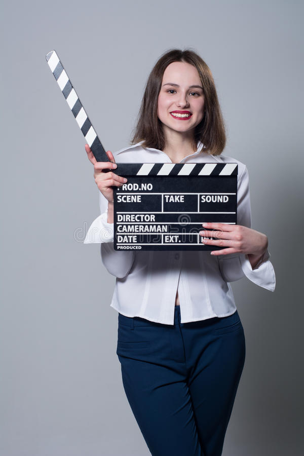 Smiling brunette in white blouse with movie crackers. Assistant director with a clapperboard on a gray background stock photography