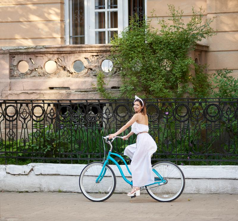 Smiling brunette in white dress riding vintage blue bike down green old street. stock images