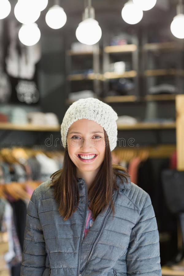 Smiling brunette with winter clothes looking at camera royalty free stock photography