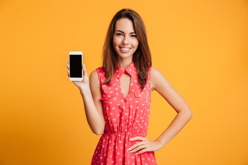 Smiling brunette woman in dress with arm on hip. Showing blank smartphone screen and looking at the camera over yellow background royalty free stock images