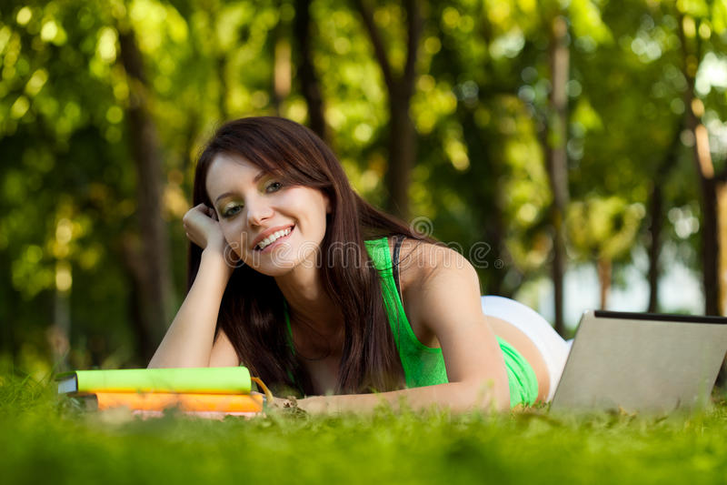 Smiling brunette woman laying on grass stock photos
