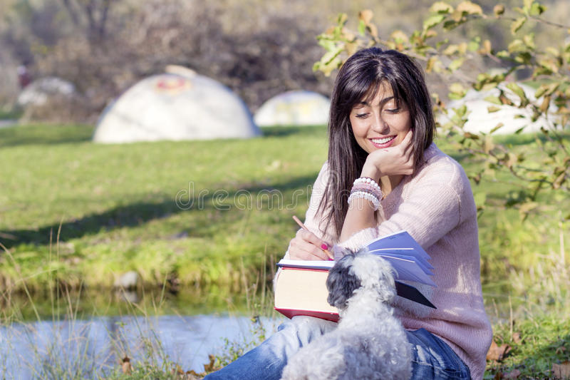 Smiling brunette woman studying in the park with her white dog. Smiling brunette woman sitting on a meadow with her dog stock photos
