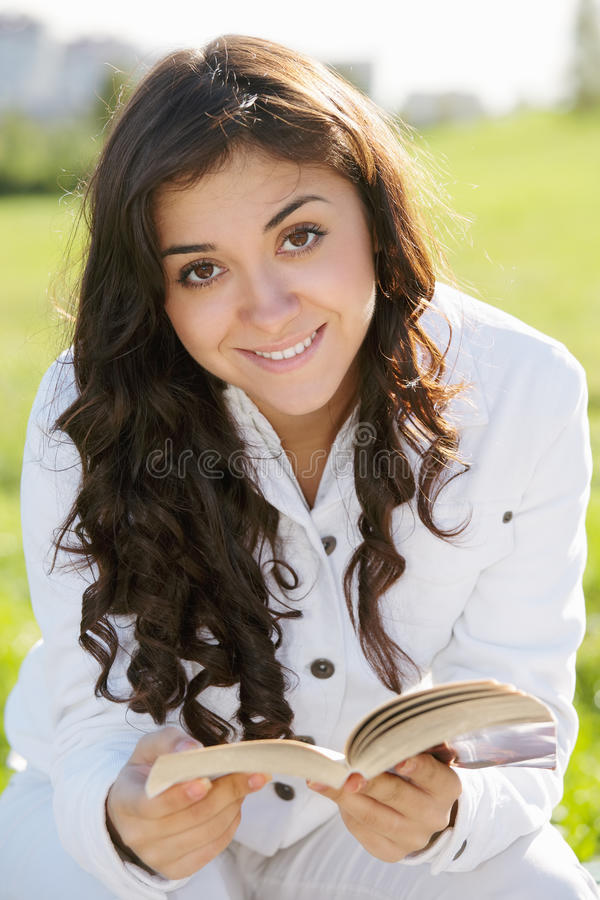 Smiling brunette woman in white with book royalty free stock photos