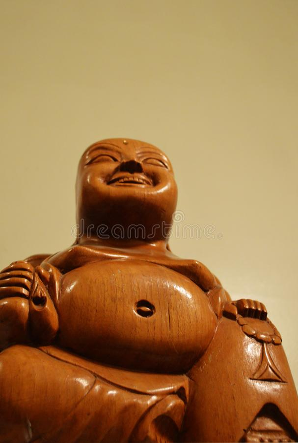 Smiling Buddha Statue, Wooden and Low Angle stock images