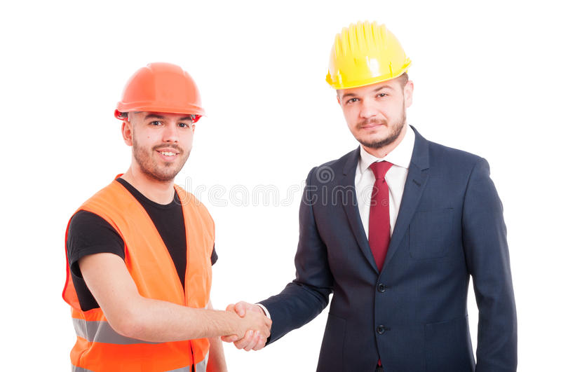 Smiling builder and businessman greeting each other royalty free stock image