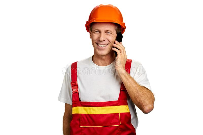 Smiling builder talking on cell phone. royalty free stock photography