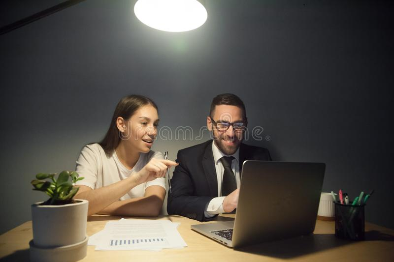 Colleagues watching funny videos in laptop during work break. Smiling business colleagues watching funny video or reading amusing article at laptop during break royalty free stock photos