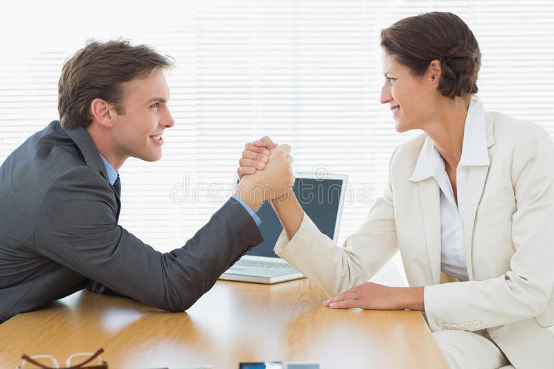 Smiling business couple arm wrestling at office desk. Side view of smiling young business couple arm wrestling at office desk stock photography