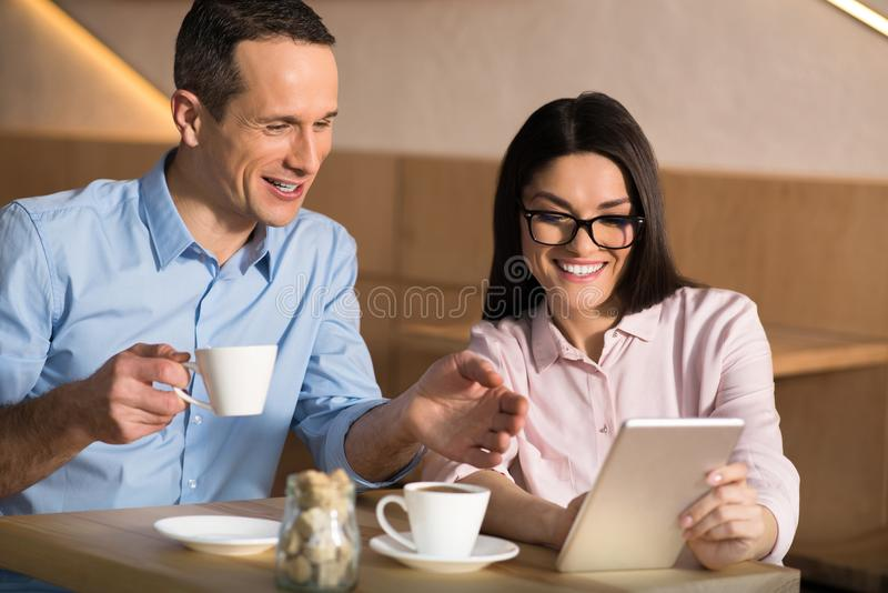 Business couple using digital tablet. Smiling business couple drinking coffee in cafe and using digital tablet royalty free stock photography