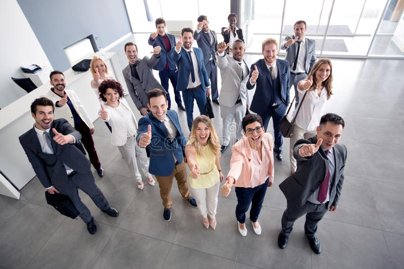 Smiling business group giving thumbs up stock photo