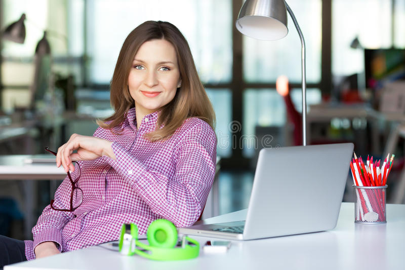 Smiling Business Lady in casual clothing sitting at Office Table. Smiling charismatic Business Lady in smart casual clothing Shirt sitting at grey Table with stock photos