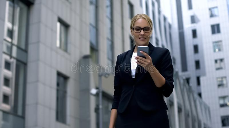 Smiling business lady got message on smartphone about discounts in brand stores. Stock photo stock images