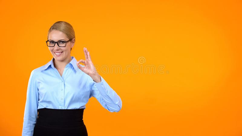 Smiling business lady showing ok gesture, excellent choice, recommendation royalty free stock photography