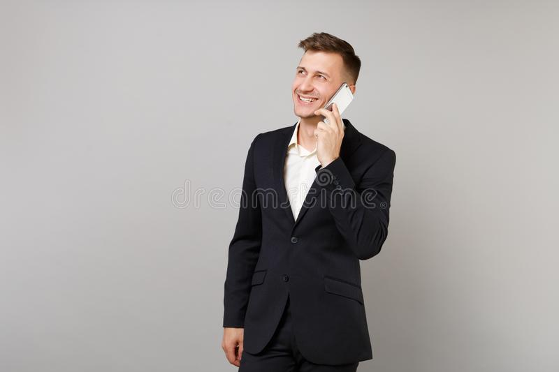 Smiling business man in classic suit looking aside talking on mobile phone conducting pleasant conversation isolated on royalty free stock photo