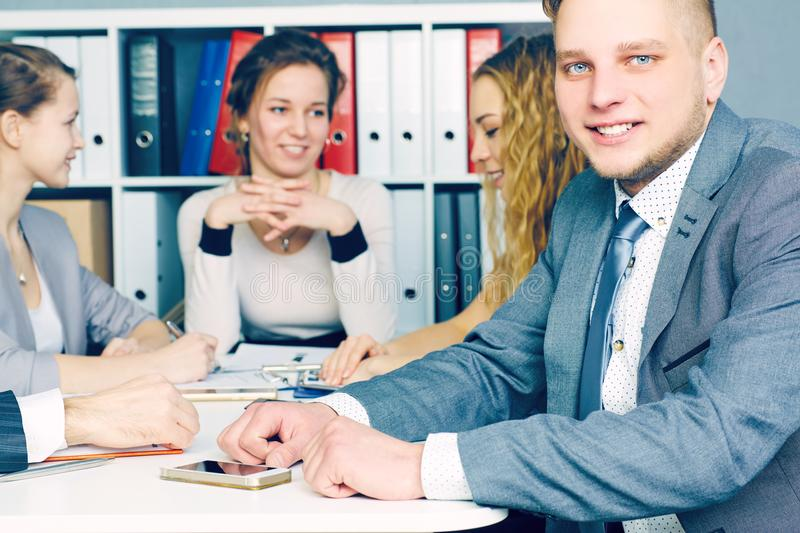 Smiling business man, with female colleagues on the background. Serious business and partnership, job offer concept. royalty free stock photos