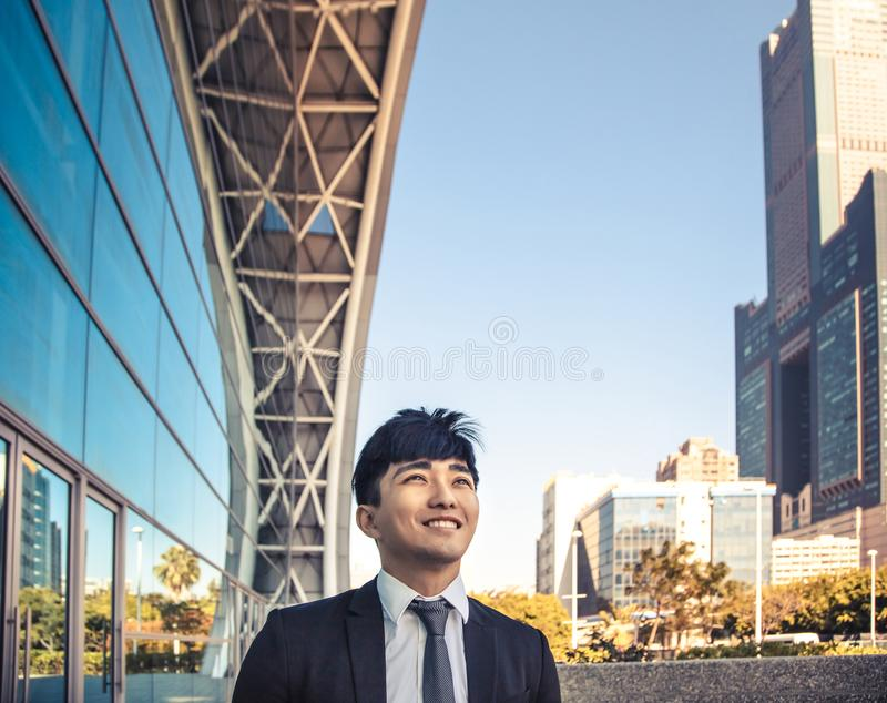 Smiling business man standing in front of  office building royalty free stock image