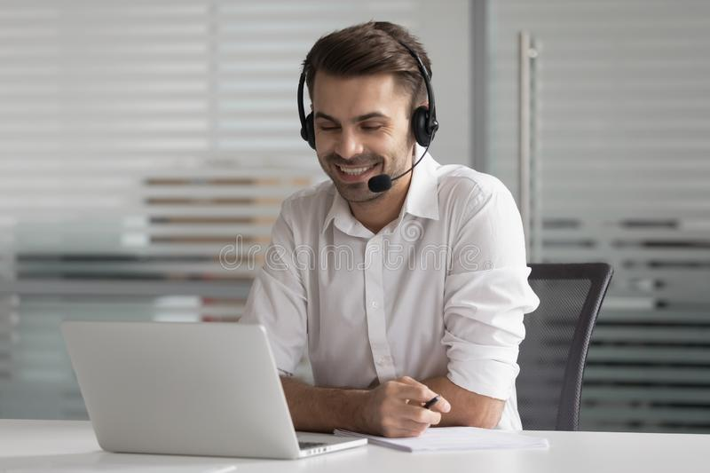 Smiling business man wearing wireless headset make conference video call. Looking at laptop screen, happy salesman customer service support agent helpline royalty free stock images