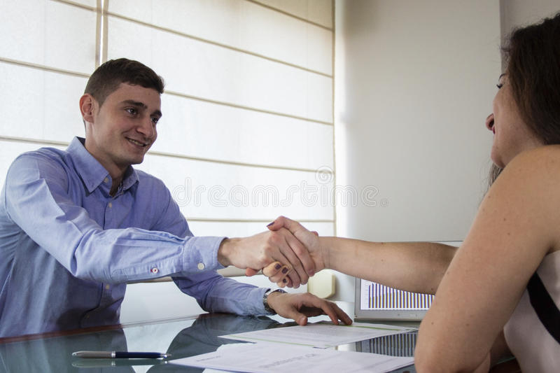Smiling business man and woman shaking hands at home office. Smiling business men and women shaking hands at home office desk stock images