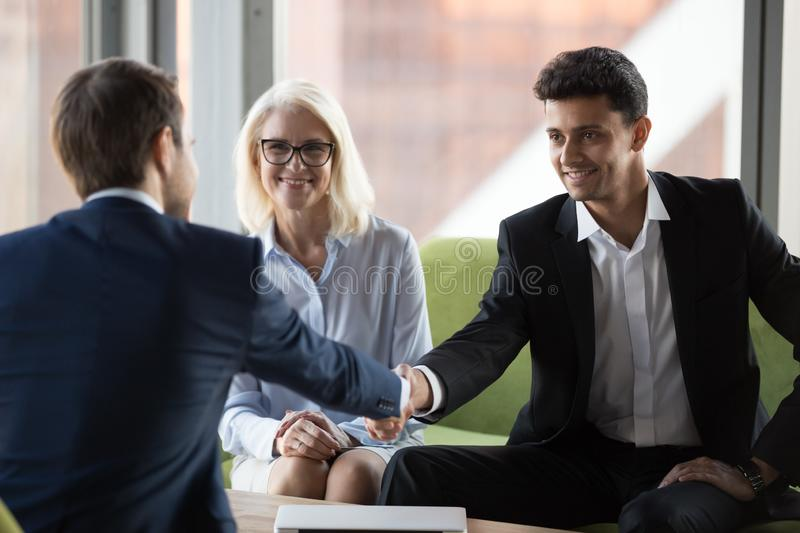 Smiling business partners handshake closing successful deal. Smiling millennial businessman shake hand of business colleague at casual office meeting, happy royalty free stock photography