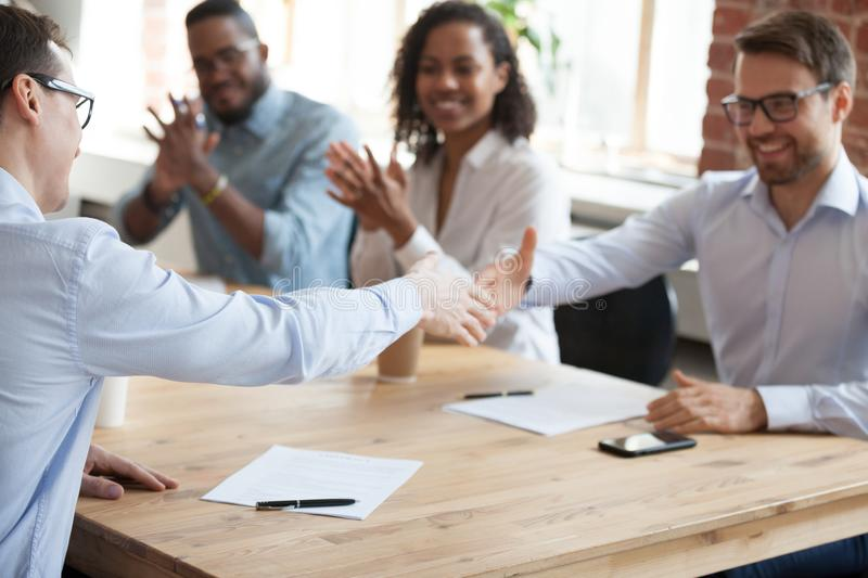 Excited employees handshake at meeting after successful negotiat royalty free stock images