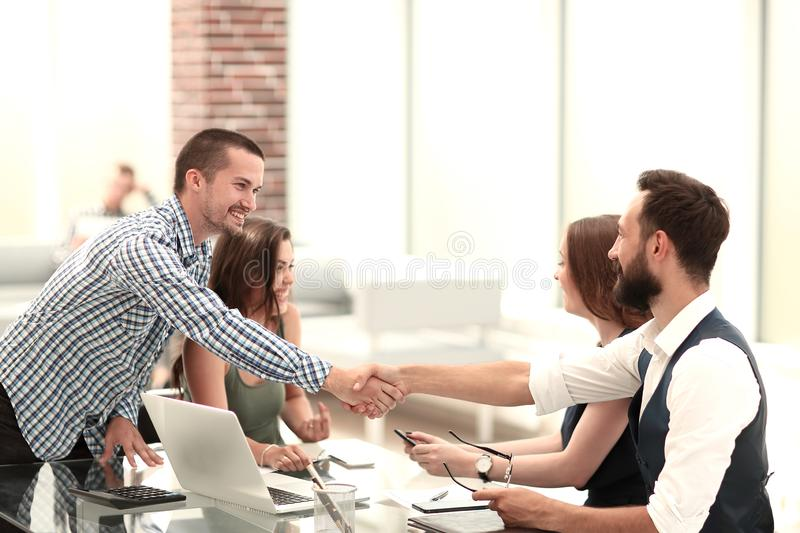 Smiling business partners shaking hands over the Desk. stock images