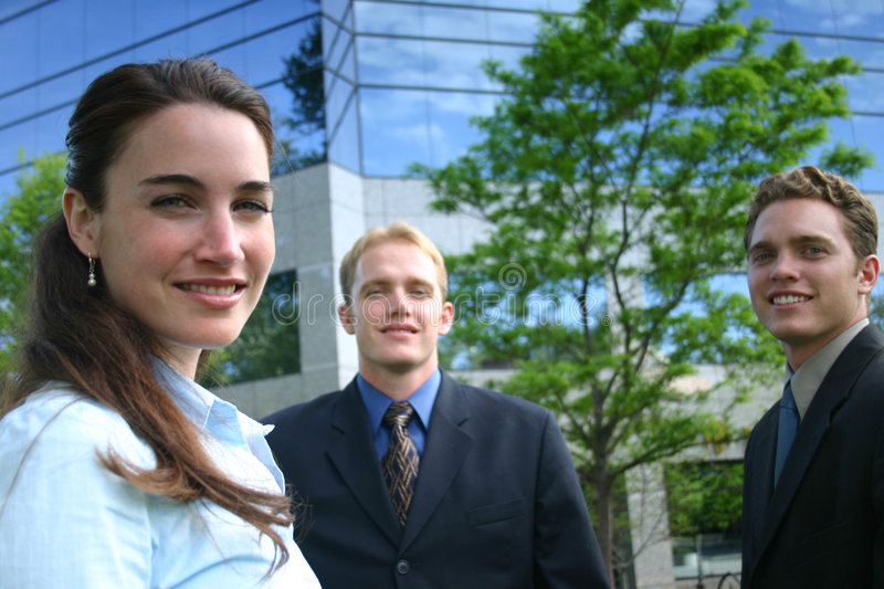 Smiling Business People. A group of three business people standing outside and smiling as they look ahead while standing in front of a business building on a royalty free stock photos